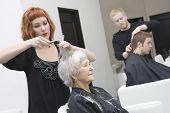 Cabeleireiros dando o corte de cabelo para os clientes no salão de beleza unisex