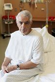image of hospital gown  - Unhappy elderly man sitting on hospital bed - JPG