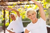 active senior woman exercising with husband outdoors
