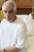 stock photo of hospital gown  - Upset elderly man sitting on hospital bed - JPG