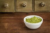 moringa leaf powder in a small bowl with a rustic drawer cabinet