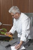 Male chef holding carrots and writing in notebook at commercial kitchen