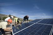 Group of multiethnic engineers lifting heavy solar panel against blue sky