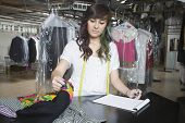 Beautiful laundry owner with notepad checking clothes at counter