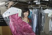 Portrait of happy female owner displaying clean dress in laundry