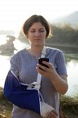 Woman With A Broken Arm And Smart Phone