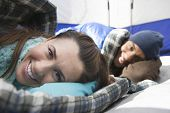 picture of sleeping bag  - Portrait of a smiling young couple lying in sleeping bags in tent - JPG