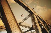 Airbourne passenger jet viewed through bridge superstructure