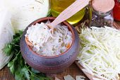 Composition with fresh and marinated cabbage (sauerkraut), spices, on wooden table background