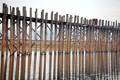 MANDALAY, MYANMAR - DECEMBER 10, 2013: Two monks are walking over U bein's Bridge in the early morni