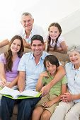 Portrait of happy multigeneration family with book at home