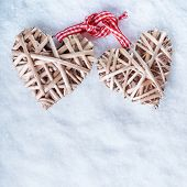 Two beautiful romantic vintage entwined beige flaxen hearts tied together with a ribbon on a white snow background. Love and St. Valentines Day concept.