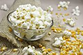 stock photo of cereal bowl  - Popcorn in bowl and kernels on a jute background - JPG