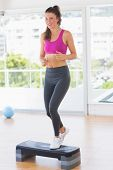 image of step aerobics  - Full length of a fit young woman performing step aerobics exercise in gym - JPG