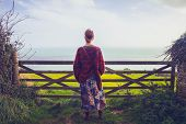 Young Woman Admiring Seaview By Rural Fence