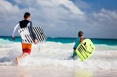 stock photo of boogie board  - Father and son running towards ocean with boogie boards - JPG