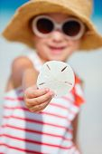 Little girl showing sand dollar she found at beach