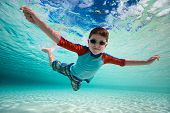 Cute little boy swimming underwater in tropical sea