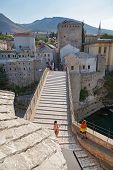 MOSTAR, BOSNIA AND HERZEGOVINA - AUGUST 9, 2012: Tourists on the Old Bridge over Neretva river. The