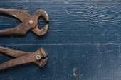 picture of tong  - old rusty tongs on blue wooden background - JPG