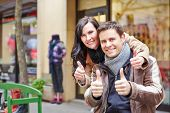 Happy couple in Berlin city holding their thumbs up