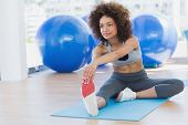 Full length of a sporty young woman stretching hands to leg in fitness studio