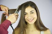 Professional Hair Dresser Ironing Long Hair Of Cute Smiling Woman