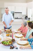 Senior man serving meal to family at dining table