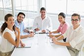 Portrait of smiling business people sitting at conference table in office