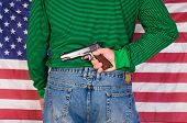 Man holding a 1911, 45 ACP behind his back in front of an American flag
