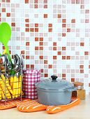 Dishes and cutlery in kitchen on table on mosaic tiles background