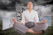Businesswoman sitting in lotus pose against stormy countryside background