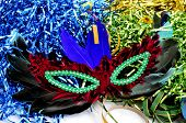 a carnival mask with feathers of different colors on a background with tinsel of different colors