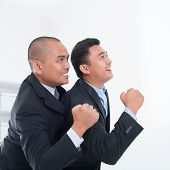 Southeast Asian businessmen celebrating success in office.