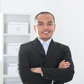 Portrait of 30s Asian Muslim business man smiling, real modern office background.