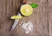 Still life with fresh lime, knife and salt on old wooden table