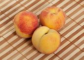 Three Ripe Peaches On Wicker Straw Mat