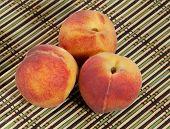 Three Ripe Red-yellow Peaches On Wicker Straw Mat