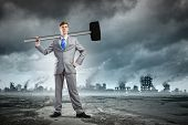 Young determined businessman with big hammer in hands