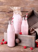 Bottles of tasty raspberry smoothie drinks on grey pink wooden background