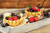 Tasty tartlets with berries on wooden tray