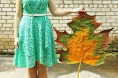 Girl holding decorative maple leaf on wall background