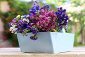 Beautiful flowers in wooden basket on table, outdoors