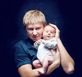 Portrait of a father and his newborn baby daughter on a black background