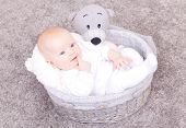 baby smiling in basket on floor