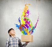 Cute boy splashing colorful paint from carton box