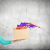 Close up of female hand holding carton box with colorful splashes