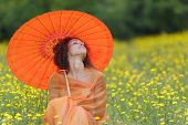 Beautiful elegant woman with an orange asian umbrella draped in a matching chiffon scarf sitting in