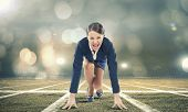 image of race track  - Young pretty businesswoman in suit ready to run - JPG