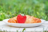 Plate with croissant and strawberry